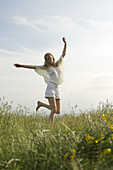 Young woman jumping in meadow
