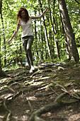 Woman walking on tree roots in woods