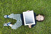 Boy lying on grass holding solar panel