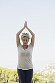 Mature woman doing sun salutation pose