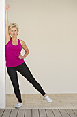 Mature woman stretching arm against wall while standing on one leg