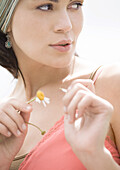 Young woman plucking petal off flower