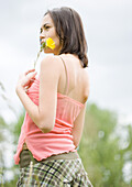 Woman holding flower, looking into distance, rear view