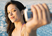 Young woman taking photo of self on beach