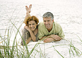 Mature couple lying on beach, front view
