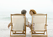 Couple sitting in beach chairs, woman turning around, looking at camera