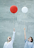 Two children holding balloons and making faces