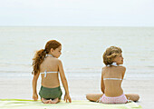 Two girls sitting on beach towel, rear view