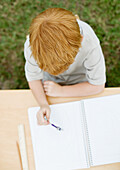 Boy sitting with open notebook