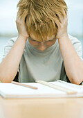 Boy holding head and looking down at homework