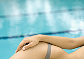 Woman lounging by side of pool, close-up of hip