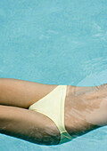 Woman floating in pool, close-up of mid section