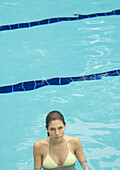 Woman standing in pool, looking at camera
