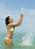 Woman standing in sea, splashing water with hands