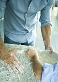 Girl and father wiping flour on counter into mixing bowl, cropped view