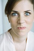 Woman making face, close-up, portrait