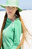 Young woman with long hair wearing sun hat on beach, waist up