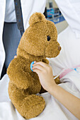 Child holding toy stethoscope to teddy bear, partial view