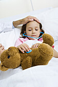Child holding toy stethoscope to teddy bear, doctor feeling child's forehead