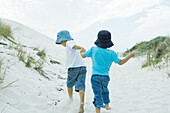 Children running through dunes, holding hands