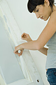 Woman removing masking tape from freshly painted woodwork on door