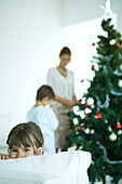 Girl looking over sofa at camera, boy and mother decorating Christmas tree in background