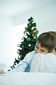 Mother sitting on sofa, holding boy in arms, Christmas tree in background, boy smiling