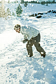 Young man bending over in snow, dodging snowball, full length