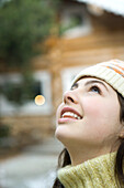 Teenage girl looking up, close-up, chalet in background