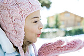 Preteen girl blowing handful of snow in mittens, side view