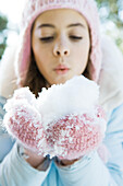 Preteen girl holding handful of snow in mittens, blowing