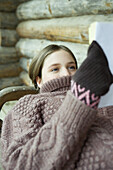 Teen girl reading book while sweater neck covers mouth