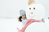 Female embracing snowman, smiling, looking down portrait