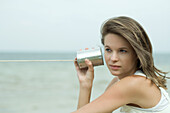 Teen girl holding tin can phone up to ear, looking away, portrait