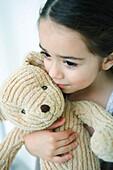Little girl holding teddy bear, looking away, portrait