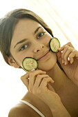 Young woman holding cucumber slices against face, smiling at camera