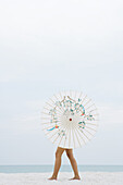 Woman behind parasol walking on beach, full length