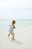 Boy on beach throwing unseen object toward ocean, rear view, full length