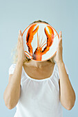 Woman holding up lobster plate in front of face