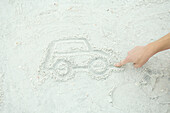 Teenage boy drawing car in sand, cropped view