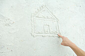 Hand drawing house in sand, cropped view