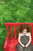 Little girl sitting on bench, eyes closed, high angle view