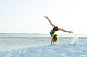 Little girl doing handstand at the beach, side view