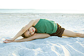 Little girl doing split at the beach, leaning over, arms raised, smiling at camera