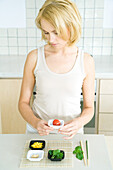 Young woman standing in kitchen, holding cherry tomato in small dish, looking down