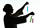 Woman holding test tubes containing different colored liquids, silhouette.