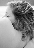Woman lying on side, close-up of bare back, shoulder and head, black and white