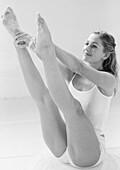 Woman sitting, extending legs up, holding heels, full length, B&W.