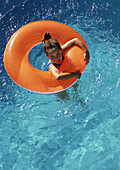 Young girl floating in inner tube in pool, shot from above.
