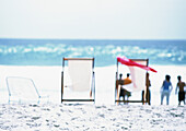Chairs on beach, adults standing in distance, blurred